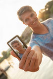Young Man Near River Taking Selfie. Young Male Near River Taking Selfie Using Smart Phone Royalty Free Stock Image