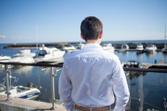Young man near the yacht club,  view from  back Royalty Free Stock Photo