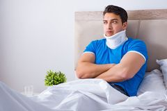 The young man with neck injury in the bed. Young man with neck injury in the bed Royalty Free Stock Photography