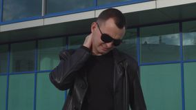 Young man with neck pain wearing leather jacket and sunglasses standing outdoor.  stock video footage