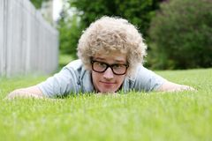 Young man with nerdy glasses laying on stomach Royalty Free Stock Photography