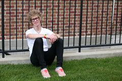 Young man with nerdy glasses sitting by fence Royalty Free Stock Photography