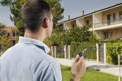 Young man and new home, door key in hand. Young man and new home; young man looking new home with door key in hand; concept of real estate Stock Photography