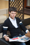 Young man with newspaper across table. Royalty Free Stock Image