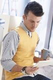 Young man with newspaper and coffee Royalty Free Stock Photos