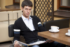 Young man with newspaper and cup of coffee Royalty Free Stock Photography