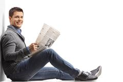 Young man with a newspaper sitting on the floor and leaning agai Stock Images