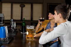 Young man next to his female friend at the bar. Young Caucasian men next to his female friend, a pretty brunette woman, sitting at the bar, drinking alcoholic stock photos