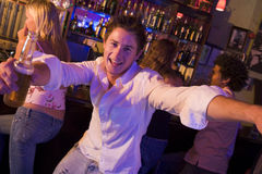 Young man in nightclub. Approaching camera with arms open holding drink Stock Photography