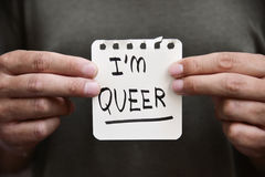 Young man with a note with the text I am queer Stock Photos
