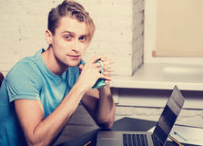 Young man with notebook laptop working on work place looking camera Stock Photos
