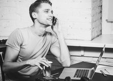 Young man with notebook laptop working on work place talking mobile phone black and white Stock Photos