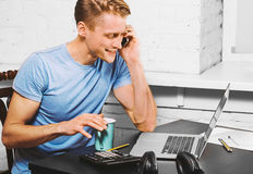 Young man with notebook laptop working on work place talking mobile phone Royalty Free Stock Images