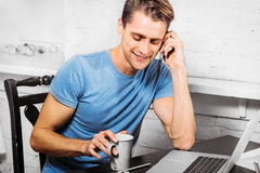 Young man with notebook laptop working on work place talking mobile phone Stock Photography