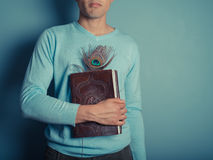 Young man with notebook and peacock feather Royalty Free Stock Image