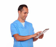 Young man in nurse uniform using tablet pc stock photos