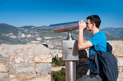 Young man on observation deck looking at panoramic view with binoculars. Stock Photo