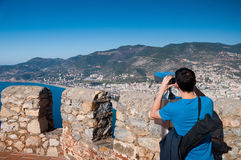 Young man on observation deck looking at panoramic view with binoculars. Royalty Free Stock Images