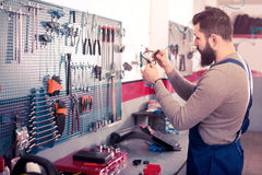 Young man is observing motorbike part for fixing. In workshop Royalty Free Stock Photography
