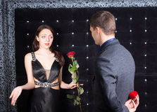 Young Man Offering a Flower to Unhappy Lady Royalty Free Stock Photos
