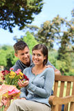 Young man offering flowers to his girlfriend Stock Photos