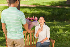 Young man offering flowers to his wife Royalty Free Stock Photo