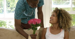 Young man offering flowers to woman stock video footage