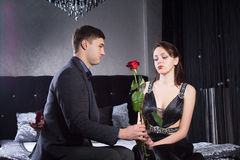 Young Man Offering Rose Flower to Sad Girlfriend Stock Photos