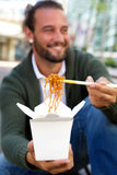 Young man offering take out noodles with chopsticks Royalty Free Stock Photos
