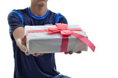 Young man offering a white gift with red ribbon to you. Isolated Stock Images