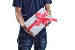Young man offering a white gift with red ribbon to you. Isolated Stock Photography