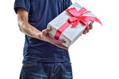 Young man offering white gift with red ribbon to you. Isolated Stock Photography