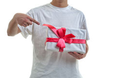 Young man offering white gift with red ribbon to you. He is po Royalty Free Stock Images