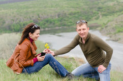 Young man offering yellow wildflowers to a girl Stock Images