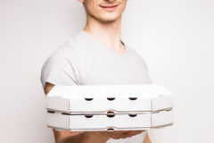 Young man offers boxes with pizza. Royalty Free Stock Image