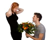 Young man offers his girlfriend flowers Royalty Free Stock Photo