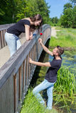 Young man offers red rose to attractive girl on bridge Royalty Free Stock Images