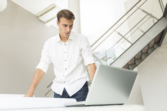 Young man in the office. Young man on the computer in the office Royalty Free Stock Photography