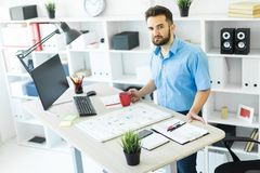The young man is in the office at the computer table, drinking coffee and working with a magnetic Board. royalty free stock photo