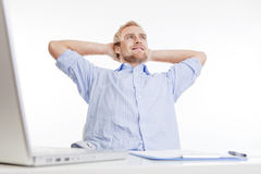 Young man at office daydreaming. Young man at office, sitting leaning back, daydreaming, smiling Royalty Free Stock Images