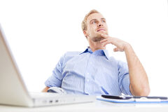 Young man at office daydreaming. Young man at office, sitting leaning back daydreaming Stock Photography