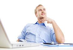 Young man at office daydreaming. Young man at office, sitting leaning back daydreaming, smiling Royalty Free Stock Image