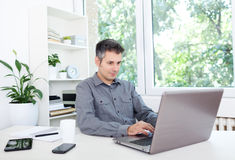 Young man at office desk, working on laptop Stock Photo