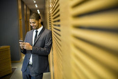 Young man in the office. Handsome young black man with mobile phone in the office Stock Photos