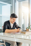 Young man in office. With phone Royalty Free Stock Image
