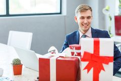 A young man in the office receives a gift. A young happy man in the office during business hours receives a gift from the ring. Many gifts. Close-up Royalty Free Stock Images