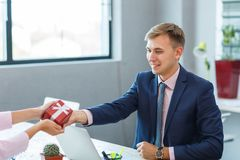 A young man in the office receives a gift. A young man in the office during business hours receives a gift from the ring. Red gift with white ribbon and bow Royalty Free Stock Photos