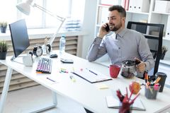 A young man in the office sits at a table, talking on the phone and holding a coffee pot. A bearded man in a light shirt and dark trousers is working in the Royalty Free Stock Photos
