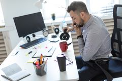 A young man in the office sits at a table, talking on the phone and pouring coffee into a cup. A bearded man in a light shirt and dark trousers is working in Stock Photo