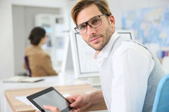 Young man at office using tablet Stock Photos